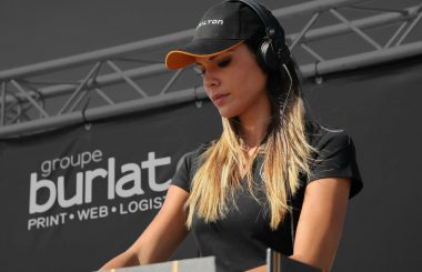 La DJ Sara Costa mixe lors d'un meeting aérien devant un fond de scène signé groupe Burlat